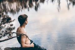 El adolescente cerca del lago se sienta en una roca Fotos de archivo libres de regalías