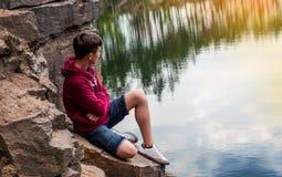 El adolescente cerca del lago se sienta en una roca Foto de archivo libre de regalías