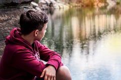 El adolescente cerca del lago se sienta en una roca Fotos de archivo