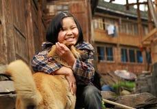El adolescente chino rural juega con el perro del jengibre, cerca de a Fotos de archivo libres de regalías
