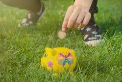 El adolescente coloca la moneda en la hucha a para ahorrar para el futuro imagenes de archivo