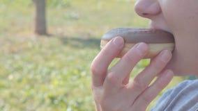 El adolescente come el buñuelo al aire libre almacen de video
