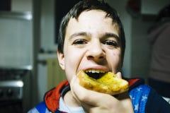 El adolescente come la rebanada de pan con el atasco para el bocado Foto de archivo libre de regalías