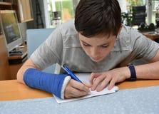 El adolescente con el brazo en yeso hace la preparación de la escuela Foto de archivo
