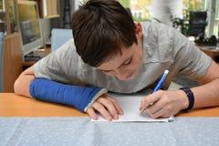 El adolescente con el brazo en yeso hace la preparación de la escuela Fotografía de archivo