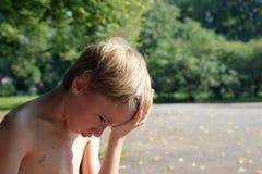 El adolescente con dolor de cabeza se sienta en un parque Foto de archivo