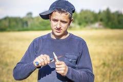 El adolescente con el cuchillo en un campo Foto de archivo libre de regalías