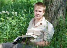 El adolescente con el libro en parque. Retrato Fotos de archivo libres de regalías