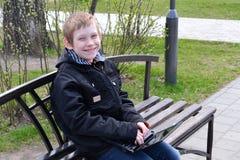 El adolescente con el ordenador portátil Fotos de archivo libres de regalías