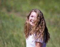 El adolescente con el pelo largo ríe en la sol Foto de archivo libre de regalías