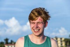 El adolescente con el pelo rojo goza de la playa hermosa Foto de archivo