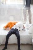 El adolescente con el peluche refiere una cama Imagenes de archivo