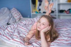 El adolescente con el teléfono mira soñador en distancia Imagen de archivo