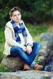 El adolescente con estilo se sienta en la roca, naturaleza al aire libre Foto de archivo libre de regalías