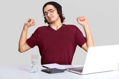 El adolescente con exceso de trabajo soñoliento prepara informe en la economía, estiramientos en la mesa, los trabajos sobre el o foto de archivo libre de regalías