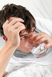 El adolescente con gripe bebe el agua Foto de archivo