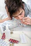 El adolescente con gripe bebe el agua Imagen de archivo