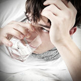 El adolescente con gripe bebe el agua Imagenes de archivo
