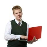 El adolescente con la computadora portátil. Fotos de archivo