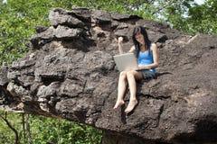 El adolescente con la computadora portátil se sienta en roca Fotografía de archivo