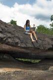 El adolescente con la computadora portátil se sienta en roca Foto de archivo libre de regalías