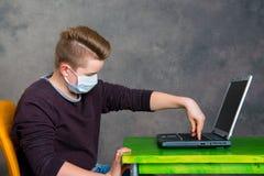 El adolescente con la máscara quirúrgica protege el ordenador contra virus Fotos de archivo libres de regalías