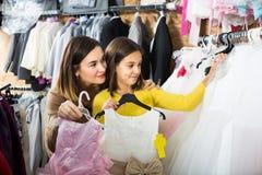 El adolescente con la madre está adquiriendo el vestido de moda Fotografía de archivo libre de regalías