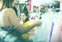El adolescente con la madre está buscando los vestidos bonitos Foto de archivo