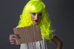 El adolescente con la peluca amarilla fluorescente, llevando una cartulina escribe Foto de archivo