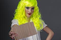 El adolescente con la peluca amarilla fluorescente, llevando una cartulina escribe Imagenes de archivo