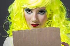 El adolescente con la peluca amarilla fluorescente, llevando una cartulina escribe Imagen de archivo libre de regalías