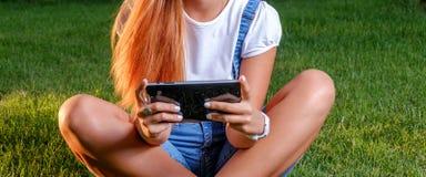 El adolescente con la tableta al aire libre cruza Imagenes de archivo