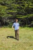 El adolescente con las gafas de sol camina feliz en el prado Fotografía de archivo libre de regalías