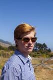 El adolescente con las gafas de sol camina feliz en el prado Imagenes de archivo