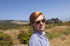 El adolescente con las gafas de sol camina feliz en el prado Imagen de archivo libre de regalías