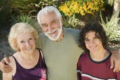 El adolescente (13-15) con los abuelos al aire libre elevó el retrato de la visión. Imagen de archivo
