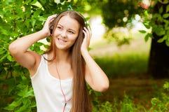 El adolescente con los auriculares acerca al árbol Imagen de archivo