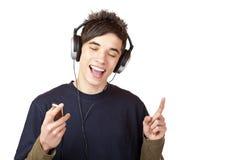 El adolescente con los auriculares escucha la música y canta Imagen de archivo