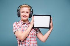 El adolescente con los auriculares muestra la exhibición del smartphone, foto con el espacio para el texto Imágenes de archivo libres de regalías
