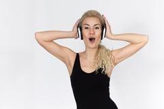 El adolescente con los auriculares que escucha la canción y canta Imagen de archivo libre de regalías