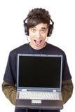 El adolescente con los auriculares sostiene el ordenador Fotografía de archivo libre de regalías