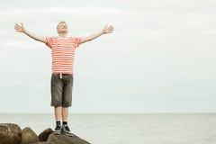 El adolescente con los brazos abiertos de par en par acerca al agua Foto de archivo libre de regalías