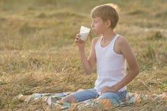 El adolescente con los ojos cerrados goza de la leche Foto de archivo libre de regalías
