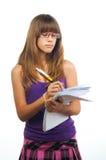 El adolescente con los vidrios escribe en el papel Fotografía de archivo libre de regalías