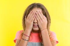 El adolescente con el pelo rubio rizado cubrió su cara con las manos, fondo amarillo brillante del estudio Imágenes de archivo libres de regalías