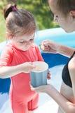 El adolescente con su pequeña hermana que pasa tiempo junto en la piscina en un jardín goza el comer del helado Foto de archivo