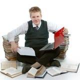 El adolescente con un montón de libros de textos. Fotografía de archivo