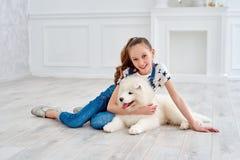 El adolescente con un perrito del samoyedo Fotos de archivo
