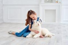 El adolescente con un perrito del samoyedo Imagenes de archivo