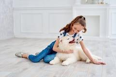 El adolescente con un perrito del samoyedo Foto de archivo libre de regalías